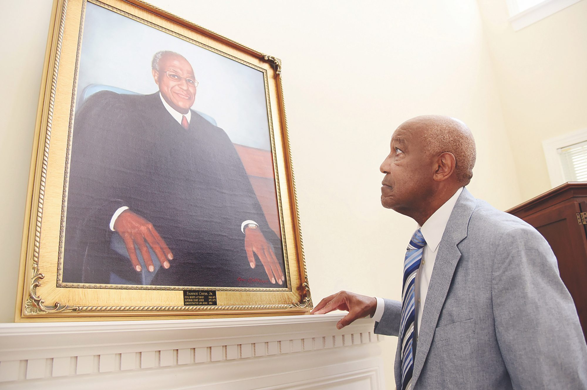 Retired Judge Sammie Chess, Jr., looks up at a painting of his portrait, a copy that hangs over the fireplace mantel at his home in Jamestown. The original painting is on display at the Guilford Country Courthouse in High Point.