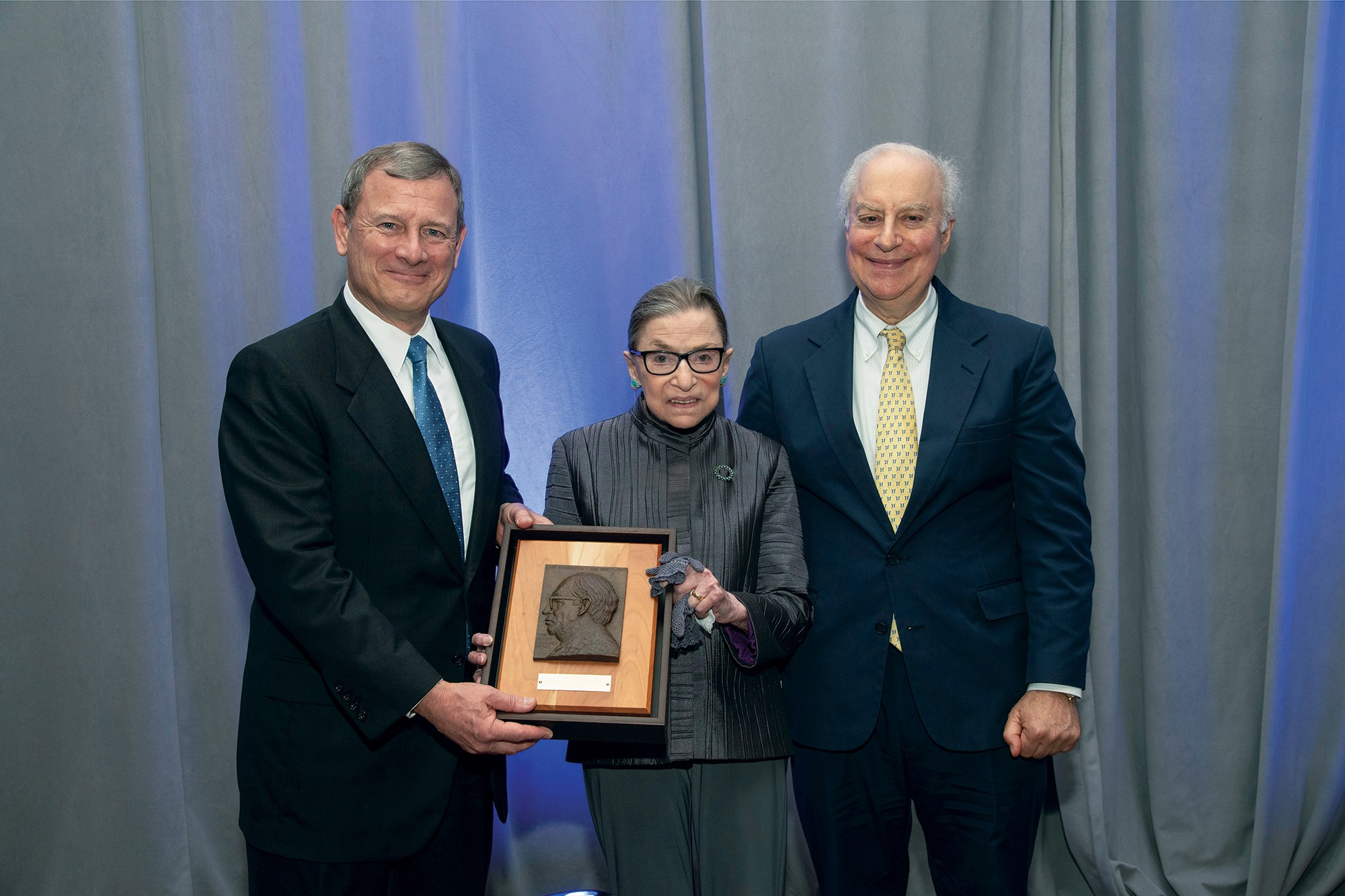 Picture of Chief Justice Roberts, Justice Ginsburg, and David F. Levi holding an award