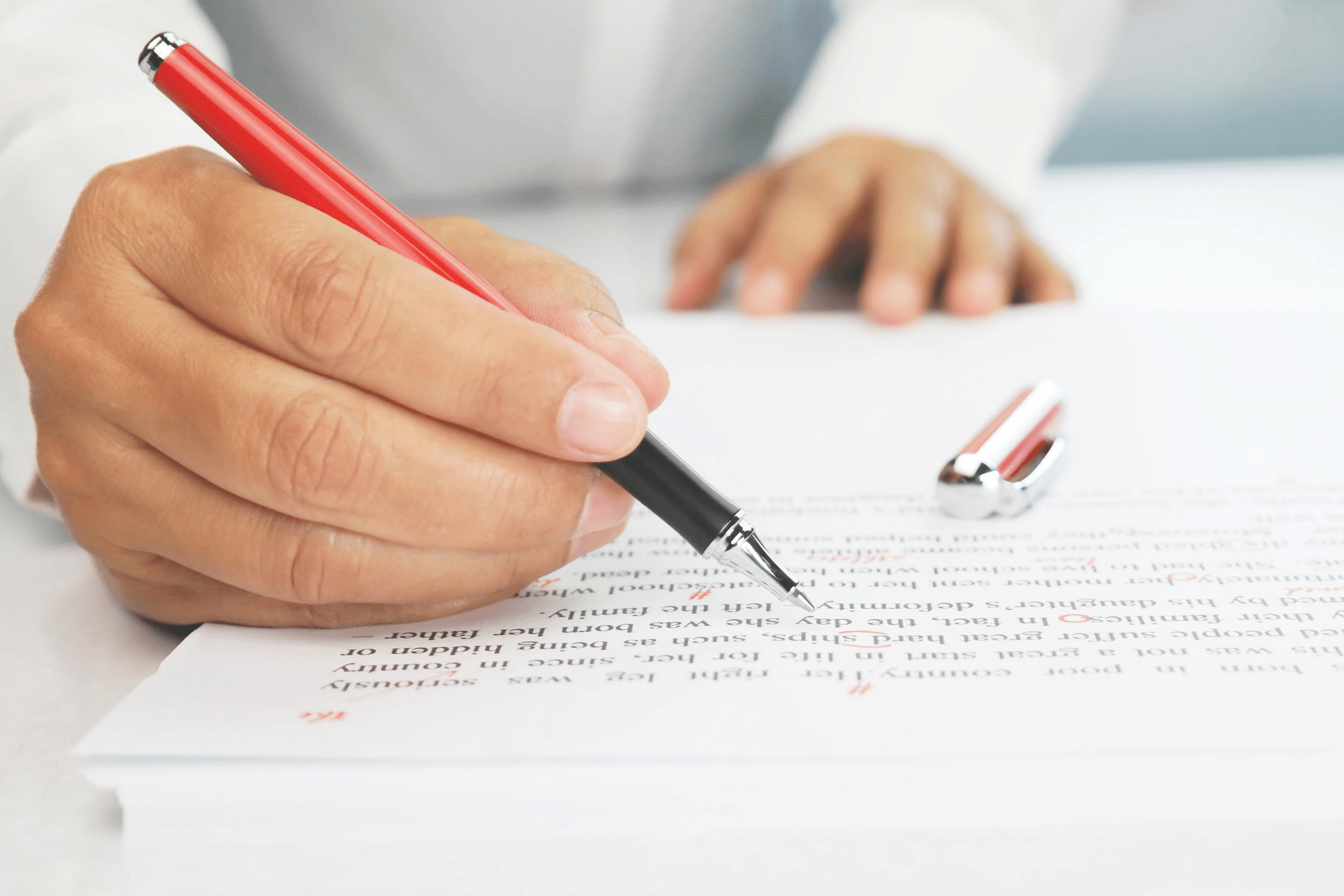 Person marking paper with red pen